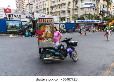 SAIGON, VIETNAM - JAN 23, 2017 - An unidentified vendor pushes a mobile kitchen on a street in the Nguyen Hue walking street