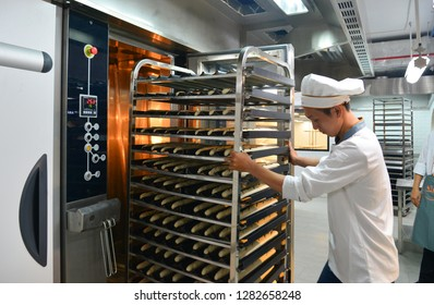 Saigon, Vietnam - Jan 9, 2018. A man working with racks of freshly baked bread at the factory in Saigon (Ho Chi Minh City), Vietnam.