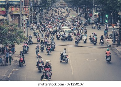 Saigon, Vietnam, January 17. 2014: Road traffic crowded with motorbikes and scooter drivers. Scooters are the most favorite vehicles in saigon. (vintage style filtered)