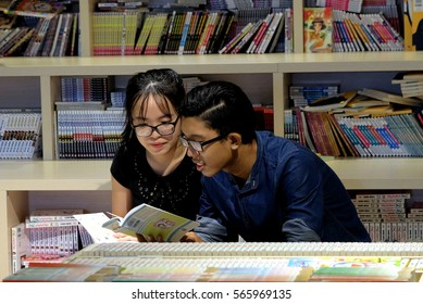 SAIGON, VIETNAM - JULY, 2016: Unidentified two young persons are reading books in the bookstore together