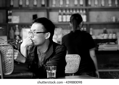 SAIGON, VIETNAM - JUNE 2016: Unidentified man with hand on chin is considering and looking far way in a coffee shop. Close up, black and white.
