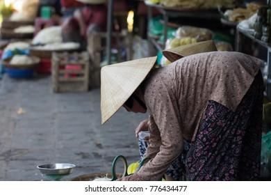 Saigon, Vietnam - June 30, 2017: senior woman in conical hat selling in market, Saigon, Vietnam.