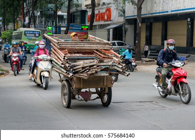 Saigon, Vietnam, Nov 2016 - Man tries to deliver a large quantity of scaffolding using an overloaded three-wheeled scooter on a busy street in Ho Chi Minh city.
