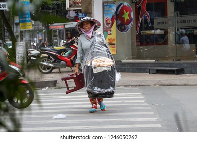 SAIGON, VIETNAM - NOV 27, 2018 - A woman street vendor crossing the road at Ho Chi Minh city with food vendor in the urban background