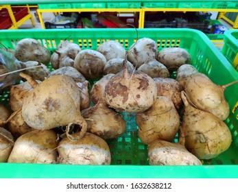 Saigon/Vietnam - Dec 01, 2019: Fresh jicama in a basket at local market, tan root vegetables, raw diet. Delicious and fresh jicama or Yam bean on supermarket shelf. Fress healthy foods for diet.