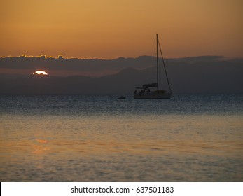 A sail boat anchored in the evening with the sun setting in the mountains in the background