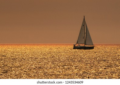Sail boat crosses ocean reflecting golden light caused by sun shining through smoke from nearby forest fire.