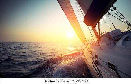 Sail boat gliding in open sea at sunset - Shutterstock ID 209357422