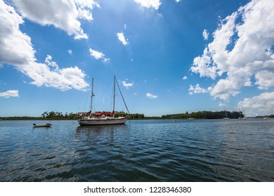 A sail boat on a lake with island behind