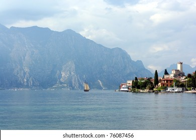 Sail boat on morning Lago di Garda lake near resort Malcesine with mountains as a background