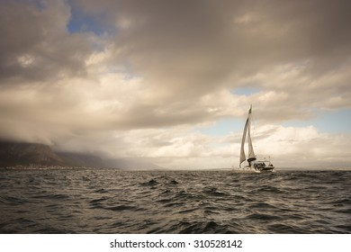 Sail boat on the open ocean on a dark cloudy day.