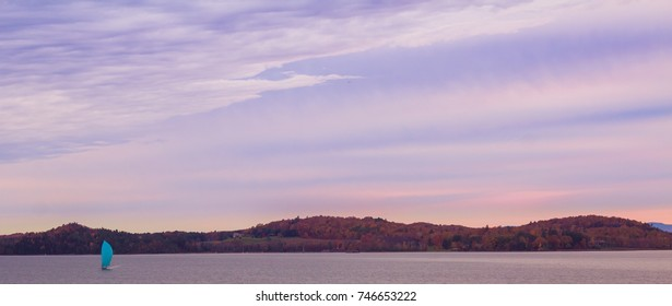 A sail boat on Shelburne Bay in Lake Champlain, Vermont during autumn colors and purple sky