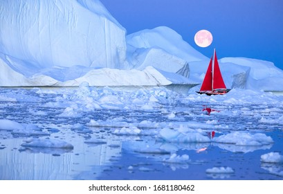 Sail boat with red sails cruising among ice bergs during dusk in front of a full moon. Disko Bay, Greenland.