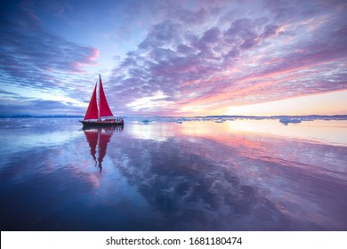 Sail boat with red sails cruising among ice bergs during sunrise. Disko Bay, Greenland. - Shutterstock ID 1681180474