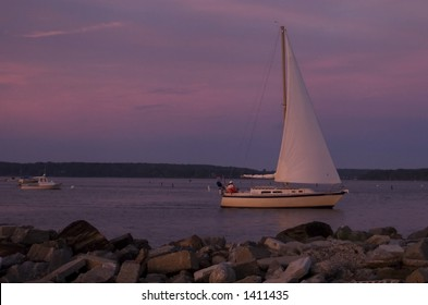 A sail boat returns to shore at sunset on the Atlantic Ocean in Portland, Maine