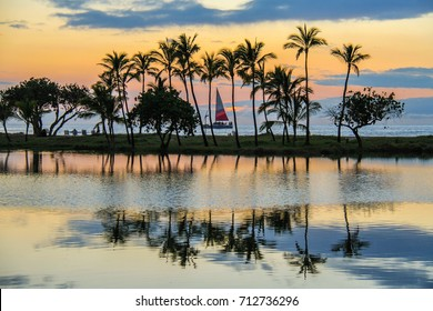 A sail boat sailing by palm trees by the Mauna Lani Resort on the Big Island of Hawaii.