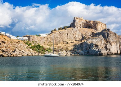 Sail boat in St. Paul´s bay, cloudy blue sky, Lindos acropolis in background (Rhodes, Greece)