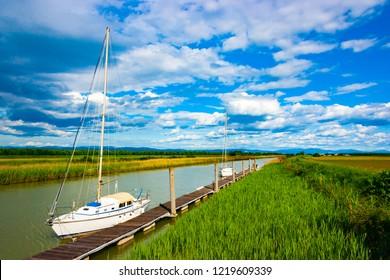 Sail boats moored to a pier on the Isonzato river near Fossalon di Grado, Friuli, Italy