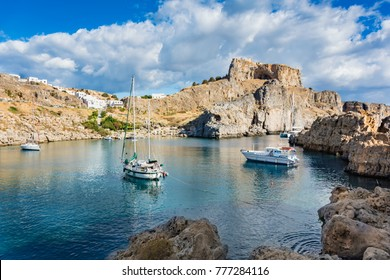 Sail boats in St. Paul´s bay, cloudy blue sky, Lindos acropolis in background (Rhodes, Greece)