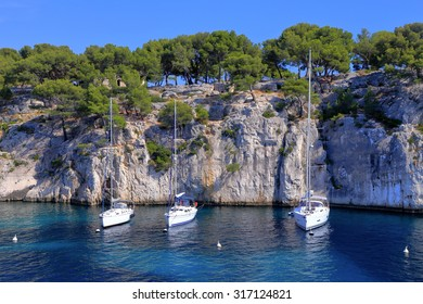 Sail boats surrounded by tall cliffs inside one of the calanques near Cassis, France