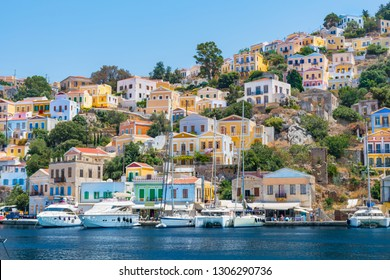 Sail boats, yachts and colorful houses in harbor town of Symi (Symi Island, Greece)