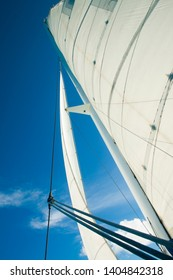 the sail and mast of the boat with the wind in favor