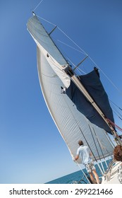 A sail on a yacht being raised against a blue summer sky.