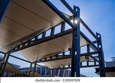 Sail shade pergola made of galvanized steel and white canvas tall standing strong structure against the blue sky