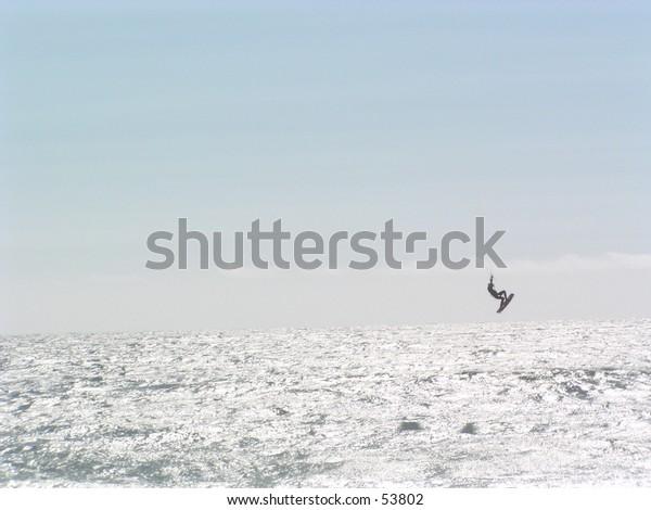 Sail surfer in a mid air trick