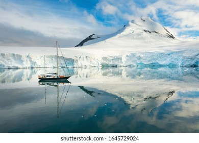 sail yacht in lagoon with calm water and reflections in Antarctica