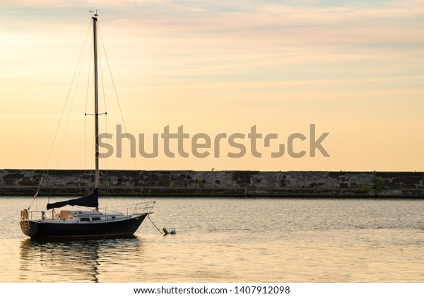 A Sailboat anchored in a bay near the breakwall at sunset.