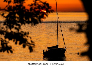 Sailboat Anchored Off an Island During Sunset. Anchored off of Lummi Island in the Puget Sound area of northwest Washington state during a dramatic sunset in the Salish Sea.