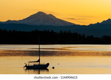 Sailboat Anchored in the Salish Sea with Mt. Baker in the Background. Sunrise in Hales Pass near Lummi Island, Washington with Mt. Baker looming large in the background.