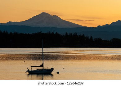 A sailboat anchors off of Lummi Island in the Puget Sound area of western Washington State. The snow capped Mt. Baker is in the background.