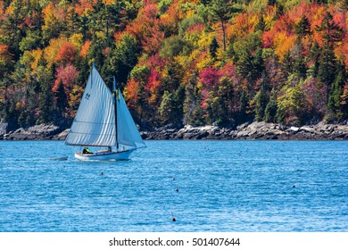 Sailboat in autumn against deep blue ocean water in coastal Maine, New England