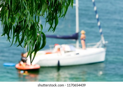 sailboat  in beach with happy family at sunset , boat unfocused