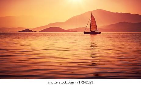 Sailboat in beautiful mild orange sunset light, sail race in Mediterranean sea, summer vacation in Turkey