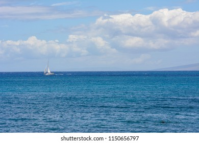 Sailboat in the beautiful water off the coast of Maui, Hawaii. The tropical island of Lanai is visible in the distance.