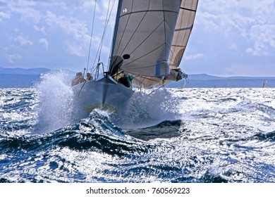 Sailboat breaking with the prow through the splashing wave on the rough sea