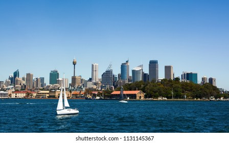 Sailboat crossing the deep blue waters of Sydney Harbor against a backdrop of the city skyline