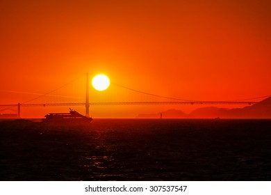 A sailboat and a ferryboat crossing the San Francisco Bay at sunset with the Golden Gate Bridge in the background.