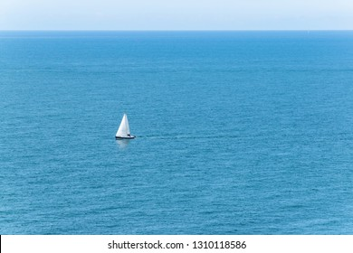 Sailboat floats alone on open sea in France at the north coast