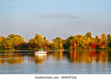 Sailboat floats on the river in autumn