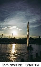 Sailboat in Front of Sun in Harbor