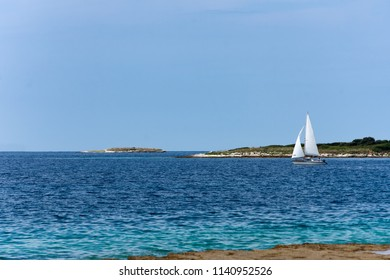 Sailboat glides across the bright blue ocean