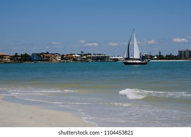 A sailboat glides toward a bay side dock on the Gulf of Mexico near St. Pete Beach, Florida.