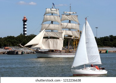 Sailboat going to open sea with full sails.Sailboat and lighthouse