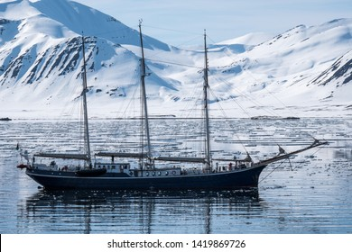 sailboat innorth polar ocean with dramatic landscape in the background at sunny day