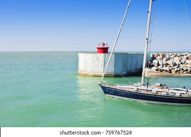 A sailboat leaves the new Pisa's harbor (Tuscany - Italy) - Image with copy space