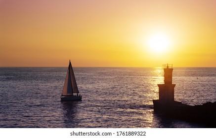 Barco de vela con faro y sol al atardecer a la salida del puerto de Pasaia, Euskadi